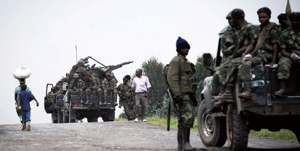 Civilians walk past trucks manned by soldiers from the Armed Forces of the Democratic Republic of the Congo (FARDC) between Goma and Rutshuru in July. AFP